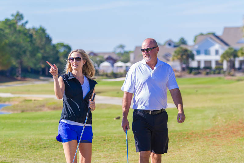 Woman pointing down fairway while man walks closely behind